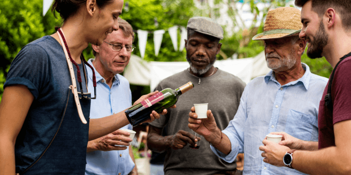 Men at an event tasting wine from a store