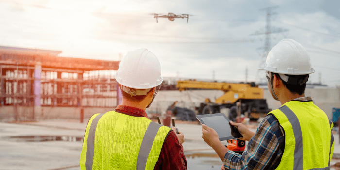 two construction workers using drone on site